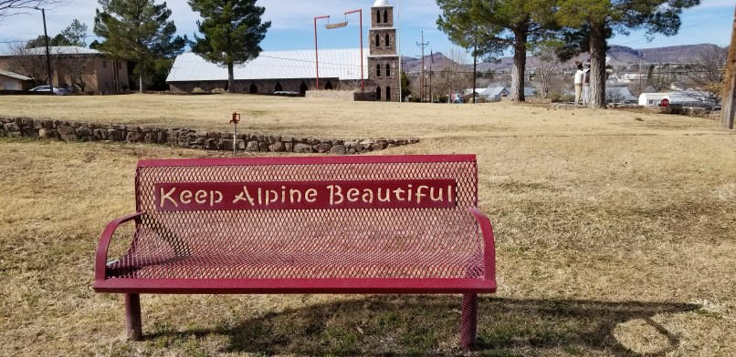 "A red bench has the words ""Keep Alpine Beautiful cut out on the metal. Behind the bench, a church is visible in the distance."