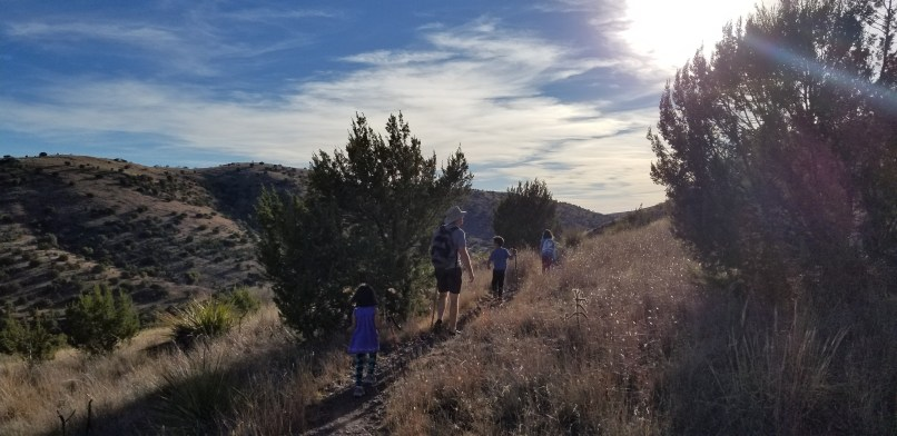 A father and three children hike up a mountain at Davis Mountain State Park