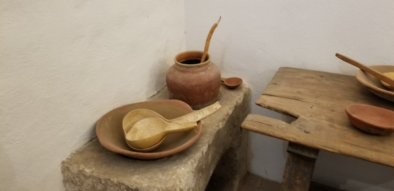 Display at San Xavier del Bac mission museum. ladles made out of gourds, pottery vases, and a stone bench sit next to a wooden table. All items are handmade from the 1800s.