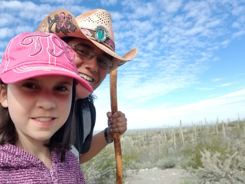 Mother and daughter selfie at Saguaro National park. The mother is wearing a pink cowboy hat with a blue brooch, and is holding a walking stick. The 9-year-old daughter is wearing a pink hat with the letters TX on it.