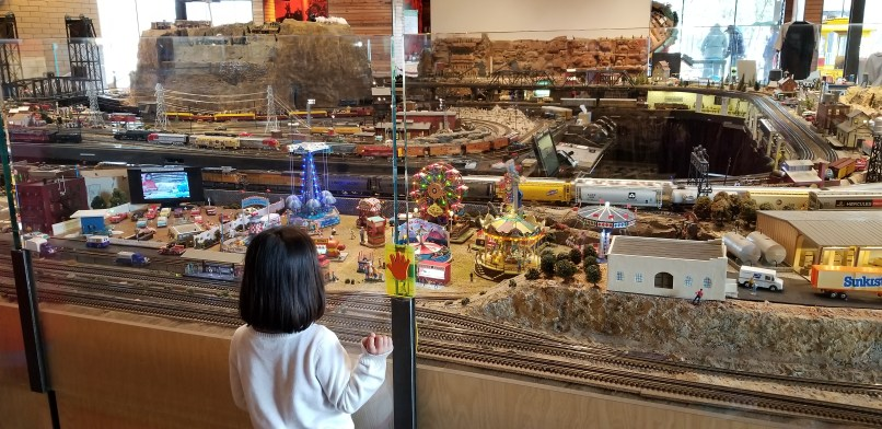 A 4-year-old girl wearing a white sweater is seen from the back, looking at a model train display at the McCormick-Stillman Model Train building.