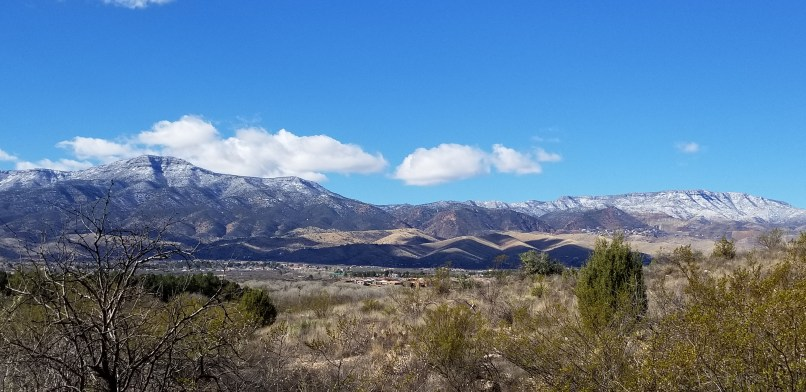 Mountain range as seen from the campground at Dead Horse Ranch State Park. Mountains can be seen in the distance, above which are blue skies and a few white clouds. In front of the mountain, some grass and small shrubs stand.