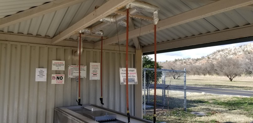 Fish cleaning station at Dead Horse Ranch State Park. Hoses hang from the ceiling, agove a stainless steel table and sink.