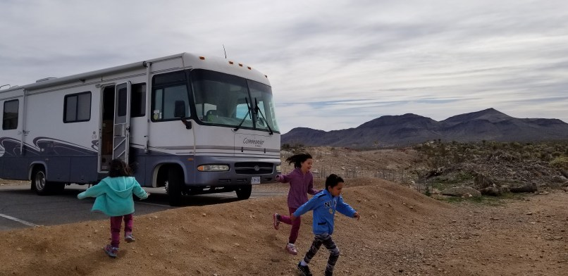Three children running down a small hill in front of a motorhome.
