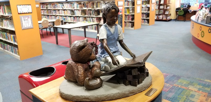 Statue of a girl reading a book while sitting next to a teddy bear and toy duck. Behind the statue are shelves of books. Statue in children's area of Rancho Cucamonga Public Library.