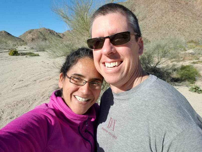 couple takes a selfie in front of mountains and trees at Joshua Tree National Park
