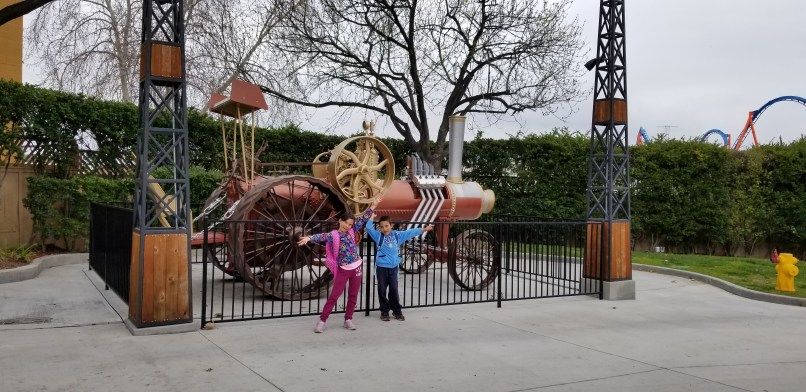 An 8-year-old girl and a 6-year-old boy standing in front of a train display at Six Flags Magic Mountain