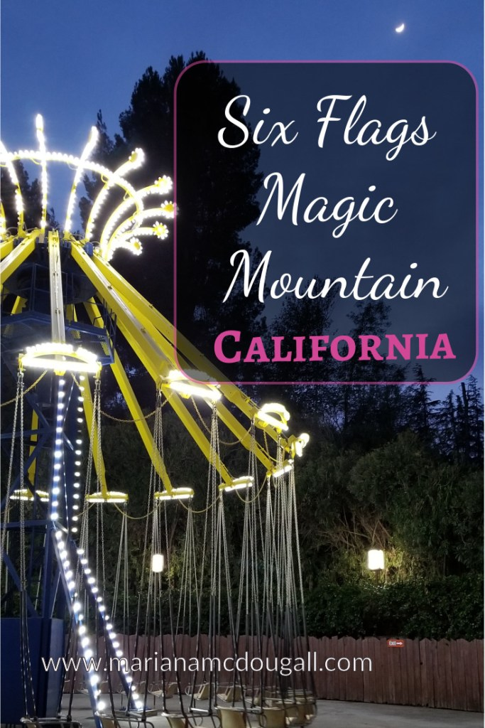 Six Flags Magic Mountain, California, www.marianamcdougall.com. Image description: Photo by Mariana Abeid-McDougall shows a swing ride in front of some trees. The photo was taken in the evening and a crescent moon can be seeing in a dark blue sky.