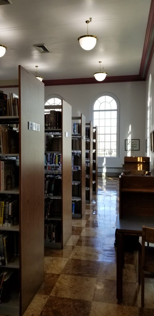 Twin Falls Public Library. Bookshelves to the left, desks to the right, and high arched windows in the middle.