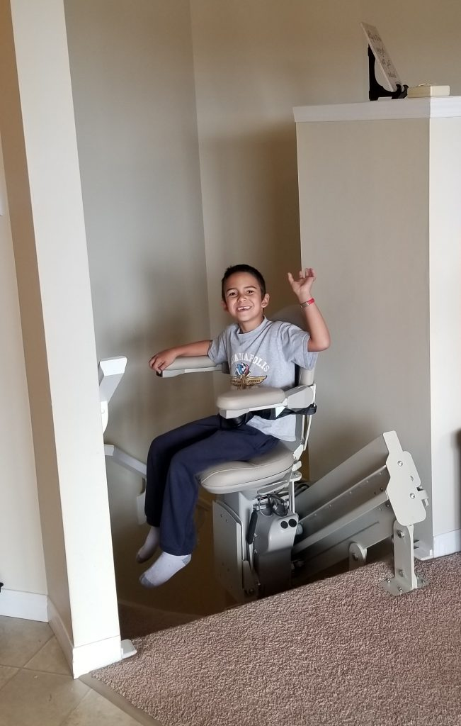 6-year-old boy sitting on a stair chairlift.