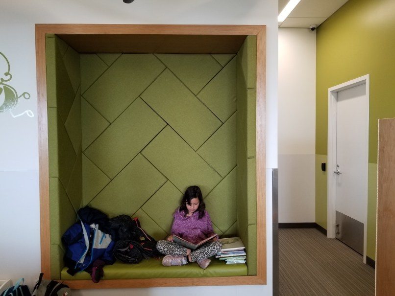 9-year-old girl sitting in a reading nook reading a book. To her left is a pile of books; to her right is a pile of winter jackets. Quarry Park Library, Calgary Public Library