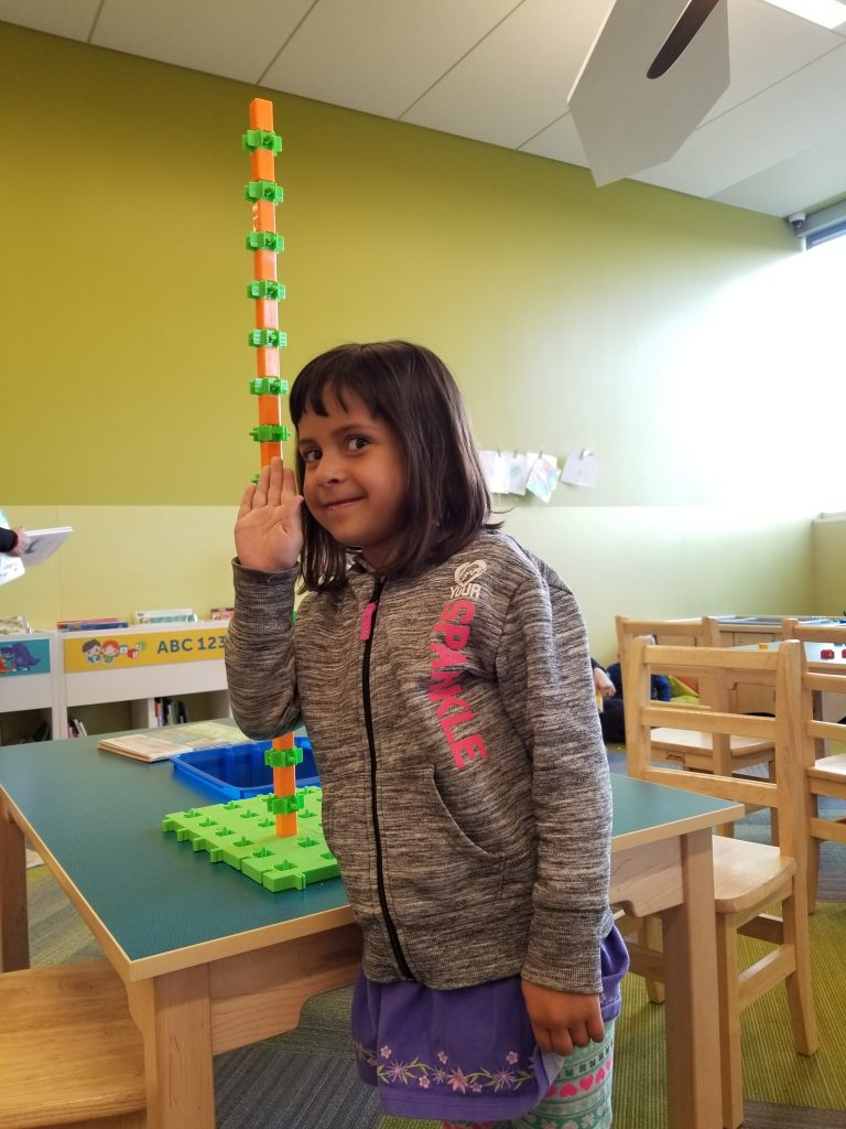 4-year-old girl stands next to a giant tower of stacking blocks at the Quarry Park branch of the Calgary Public Library