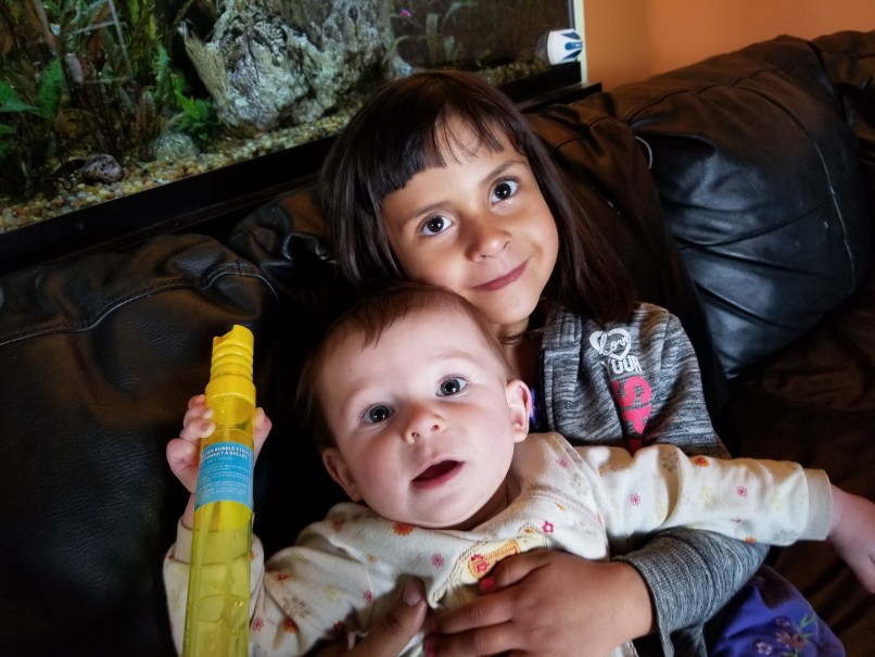 A 4-year-old girl holds a 6-month old baby while they both smile for the camera. Calgary, Alberta