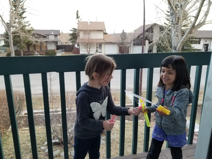 Two 4-year-old girls play with bubbles on a balcony in Calgary, Alberta