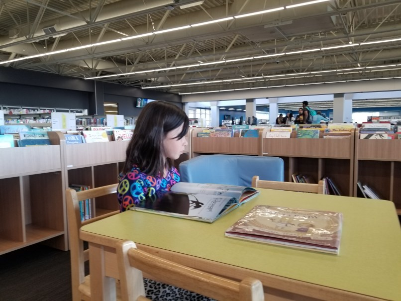A 9-year-old girl reads a book at the Crowfoot branch of the Calgary Public Library