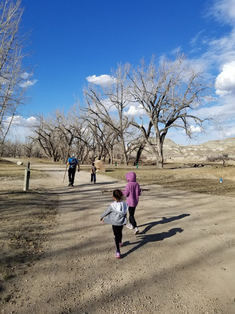 three children and their father walk along a path at Dinosaur Provincial Park
