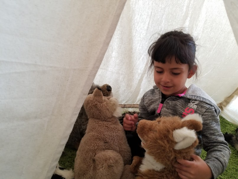 a 4-year-old girl plays with stuffed animals inside a play tent at Dinosaur Provincial Park