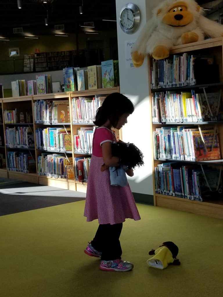 4-year-old girl holding a stuffed animal in front of a shelf of books in the Brooks, Alberta library