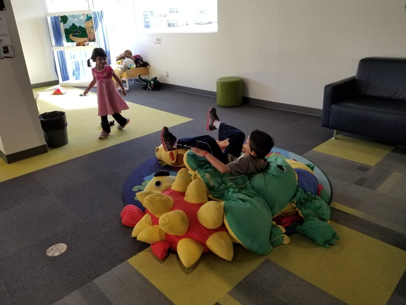 Two children playing in the children's area of the Brooks, Alberta library