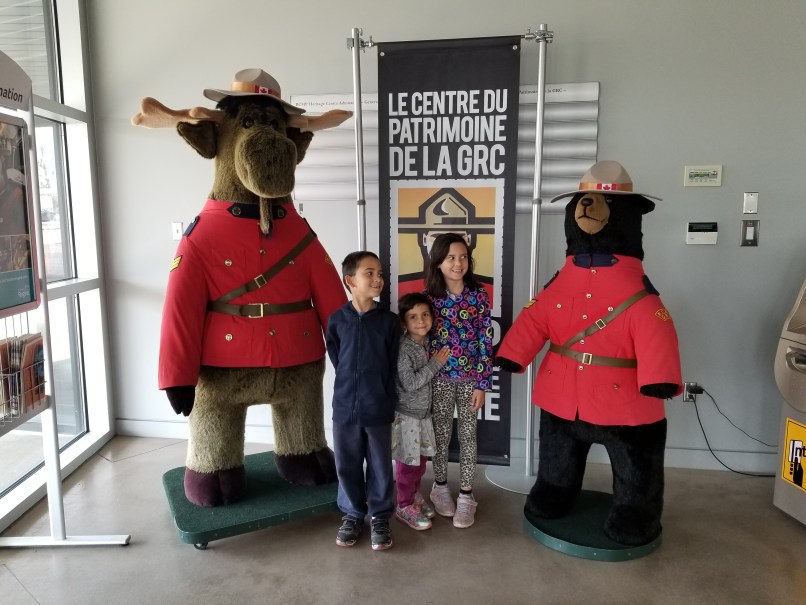 Three children standing between large stuffies of a moose and a bear in RCMP uniforms, RCMP Heritage Centre, Regina, Saskatchewan