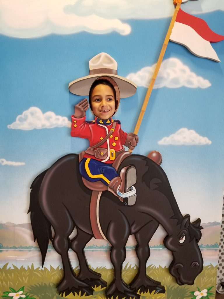 6-year-old boy with his face in a cutout poster of a cartoon mountie on a horse, RCMP Heritage Centre, Regina, Saskatchewan