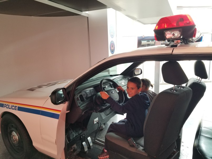 Boy sitting in driver's seat of display RCMP vehicle; girl sitting in passenger seat at RCMP Heritage Centre
