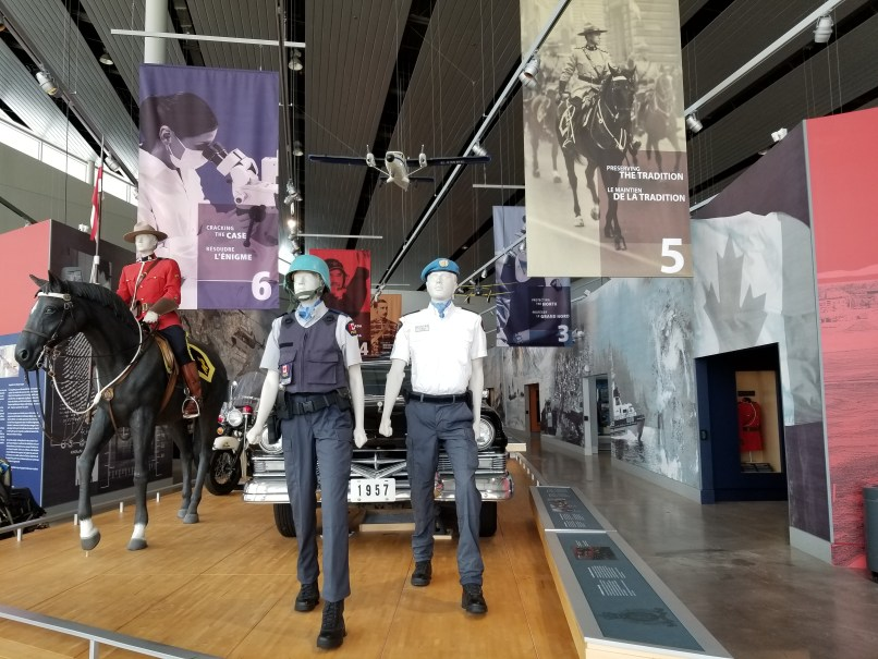 Display at RCMP Heritage Centre in Regina, Saskatchewan, showing men in various uniforms; one sitting on a horse. Behind them is a car.