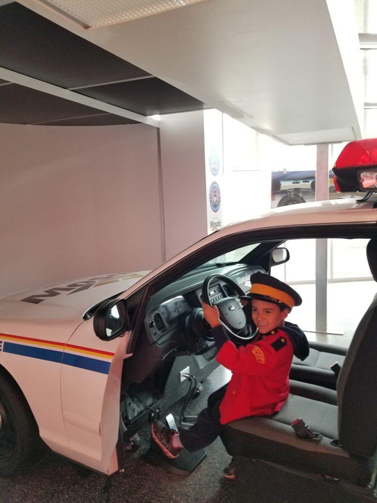 Boy sitting in driver's seat of display RCMP car at RCMP Heritage Centre, Regina, Saskatchewan