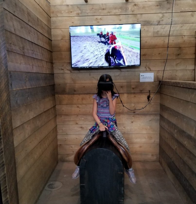 9-year-old girl sitting on a saddle on a wooden box, wearing virtual reality goggles. There is a screen behind her showing RCMP officers on horseback. RCMP Heritage Centre, Regina, Saskatchewan