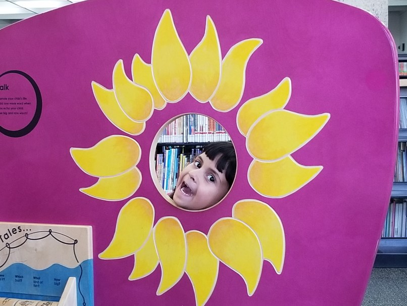 4-year-old girl in a cut-out of a sunflower.