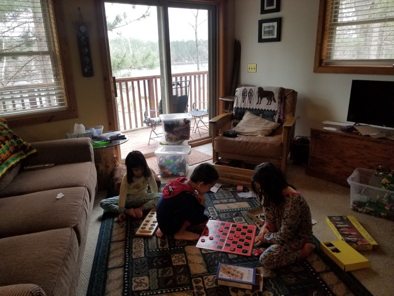 Three children playing on the floor in a cabin. Two are playing checkers while a third looks on.