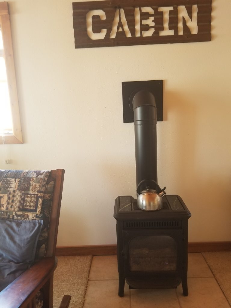 "fireplace to the right of a chair, under a sign that says ""cabin."""