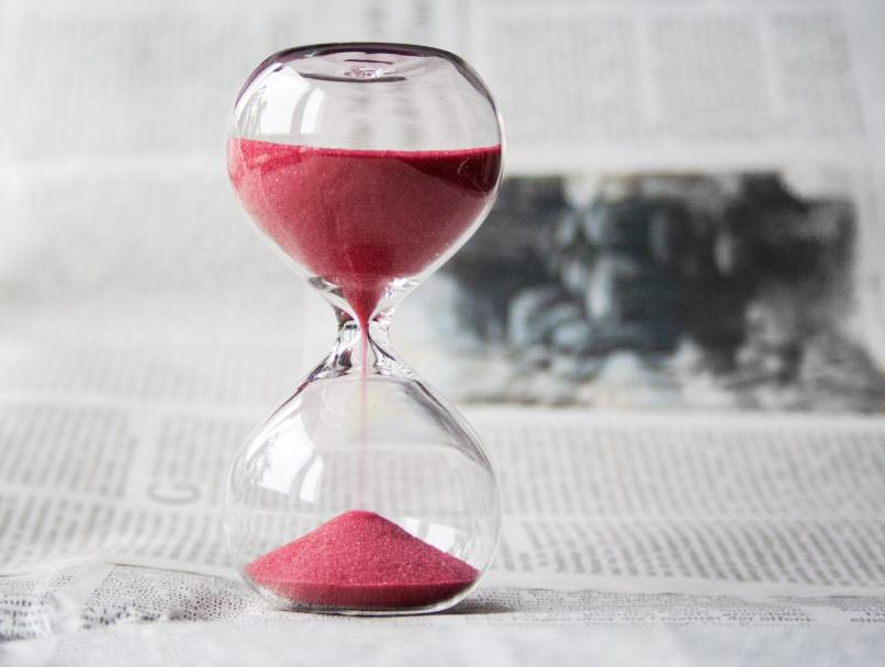 hourglass with red sand on top of a newspaper. I was able to avoid the waiting time at a walk-in clinic in Calgary by using the Maple app.