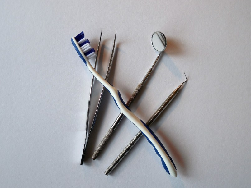 A toothbrush and some dentist tools on a white background. We were fortunate to be able to get a same-day appointment at The Smile Team Pediatric Dentist in Calgary, Alberta.