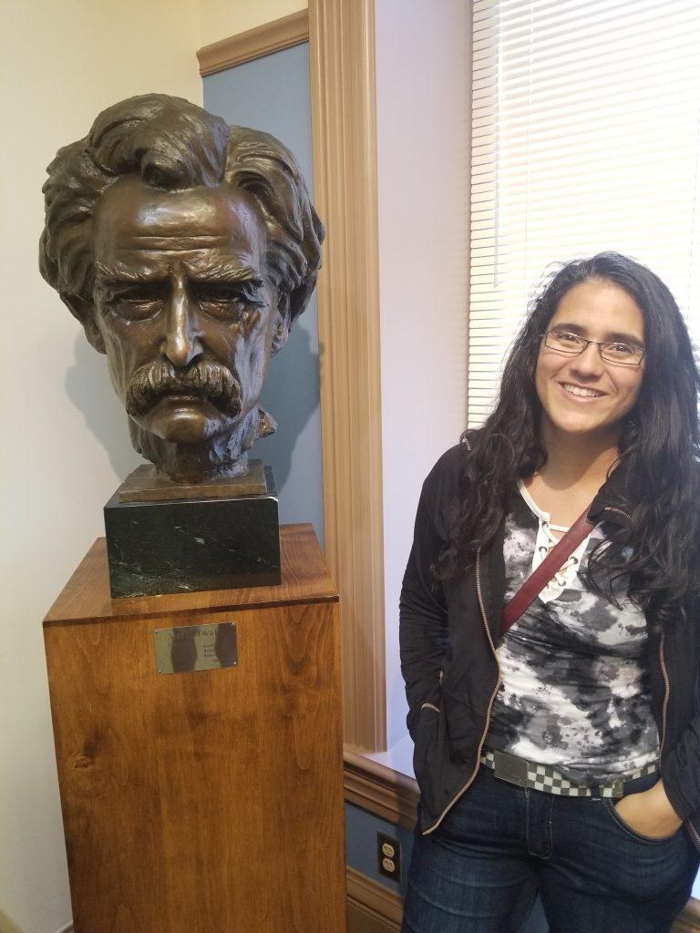 Woman beside a bust of Mark Twain