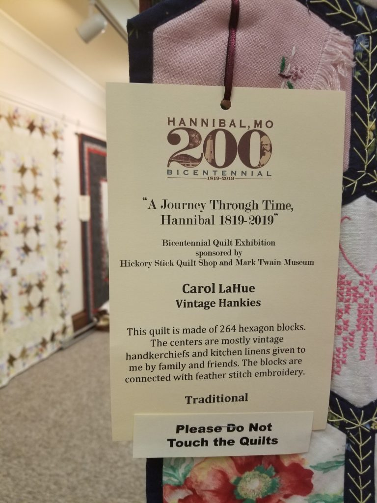 Quilt display information. The quilt is composed of 264 hexagons, connected by feather stitch embroidery.