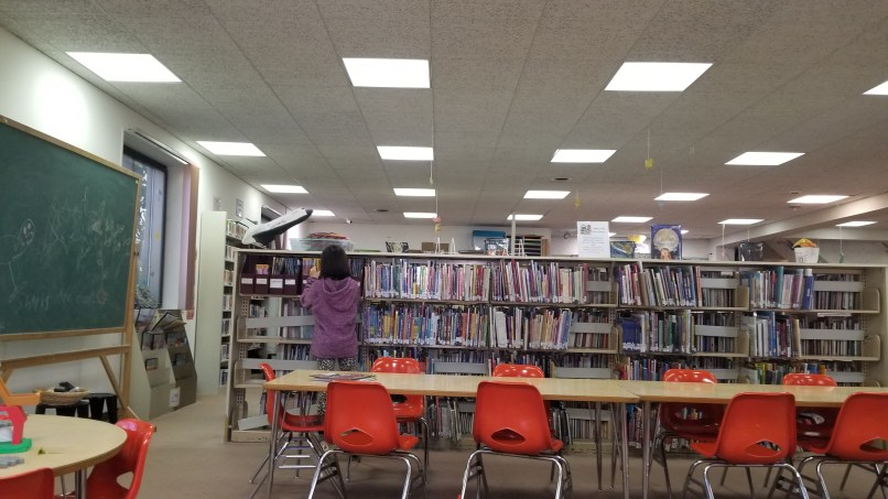 girl looking for book in library stack
