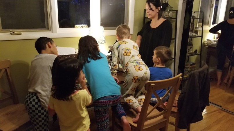 Kids around a table looking at a microscope