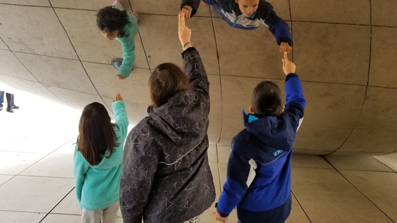 "Three children touching the underside of ""The Bean"" sculpture in Chicago"