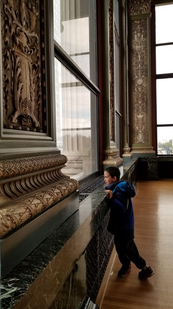 Boy standing by a window in the Chicago Cultural Center