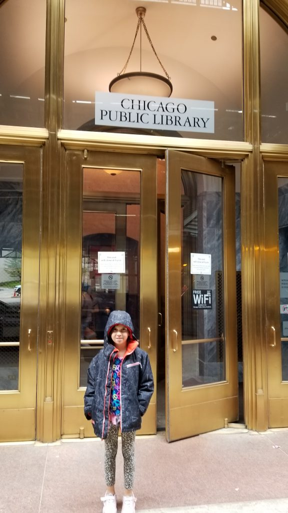 Girl in front of Chicago Public Library door downtown