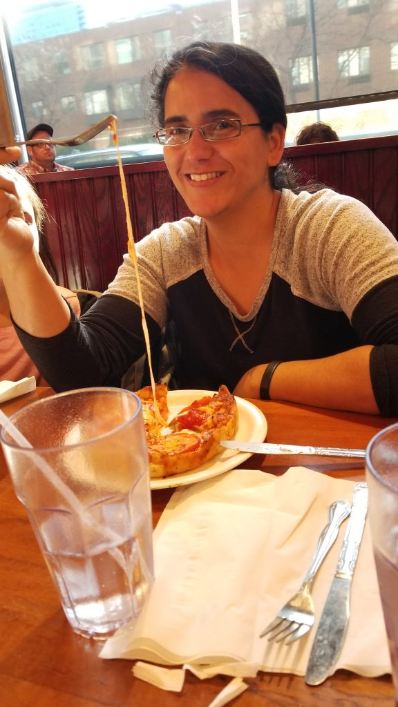 Mariana holding a fork with super stretchy mozzarella coming from her deep dish pizza at Lou Malnati's.