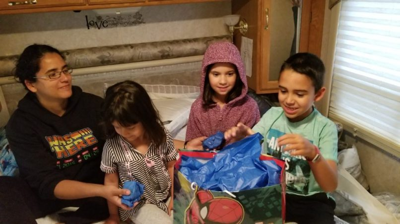Three children sitting on a bed with their mother, opening gifts.