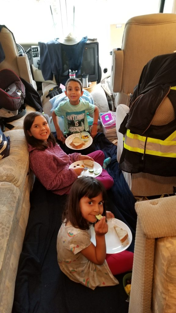Three children sitting on the floor having an indoor picnic in an RV