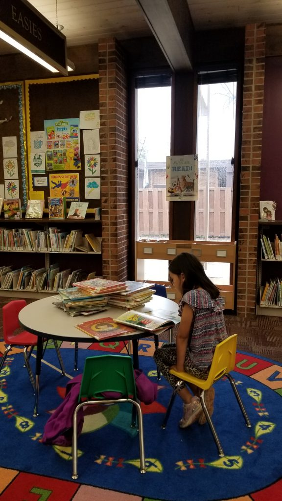 Girl sitting at a table. A large pile of books is on the table in front of her.