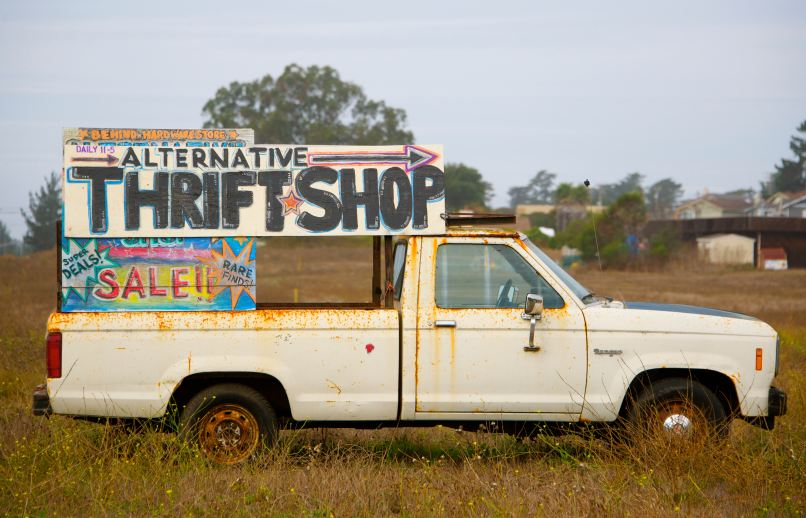 """white pickup truck with a sign that says """"alternative thrift shop sale"""" on top of the truck bed. Photo by chrissie kremer on Unsplash"""