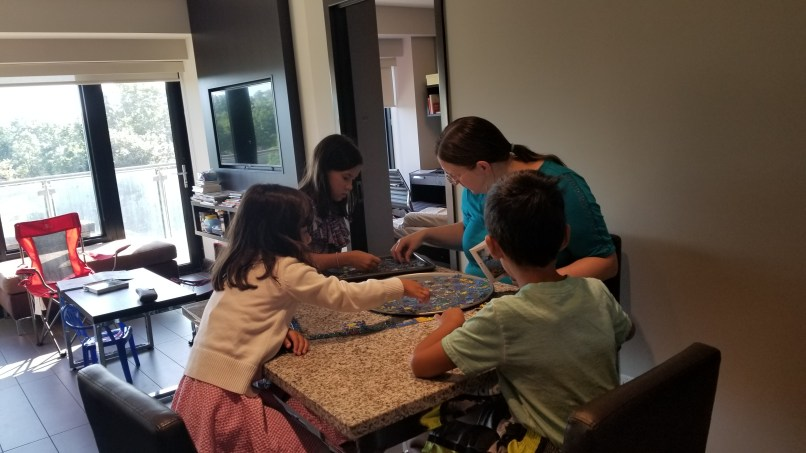 April and the kids doing a puzzle.