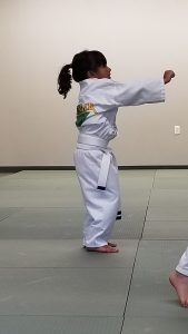 5-year-old girl in martial arts uniform, doing a jab.