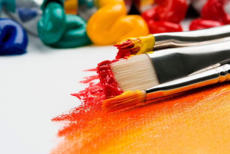paintbrushes with paints on a canvas and more pain in background. Photo by Anna Kolosyuk on Unsplash