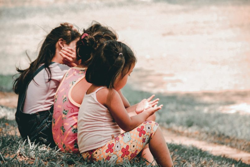 Three children sitting on the grass, as seen from the back. Photo by Charlein Gracia on Unsplash